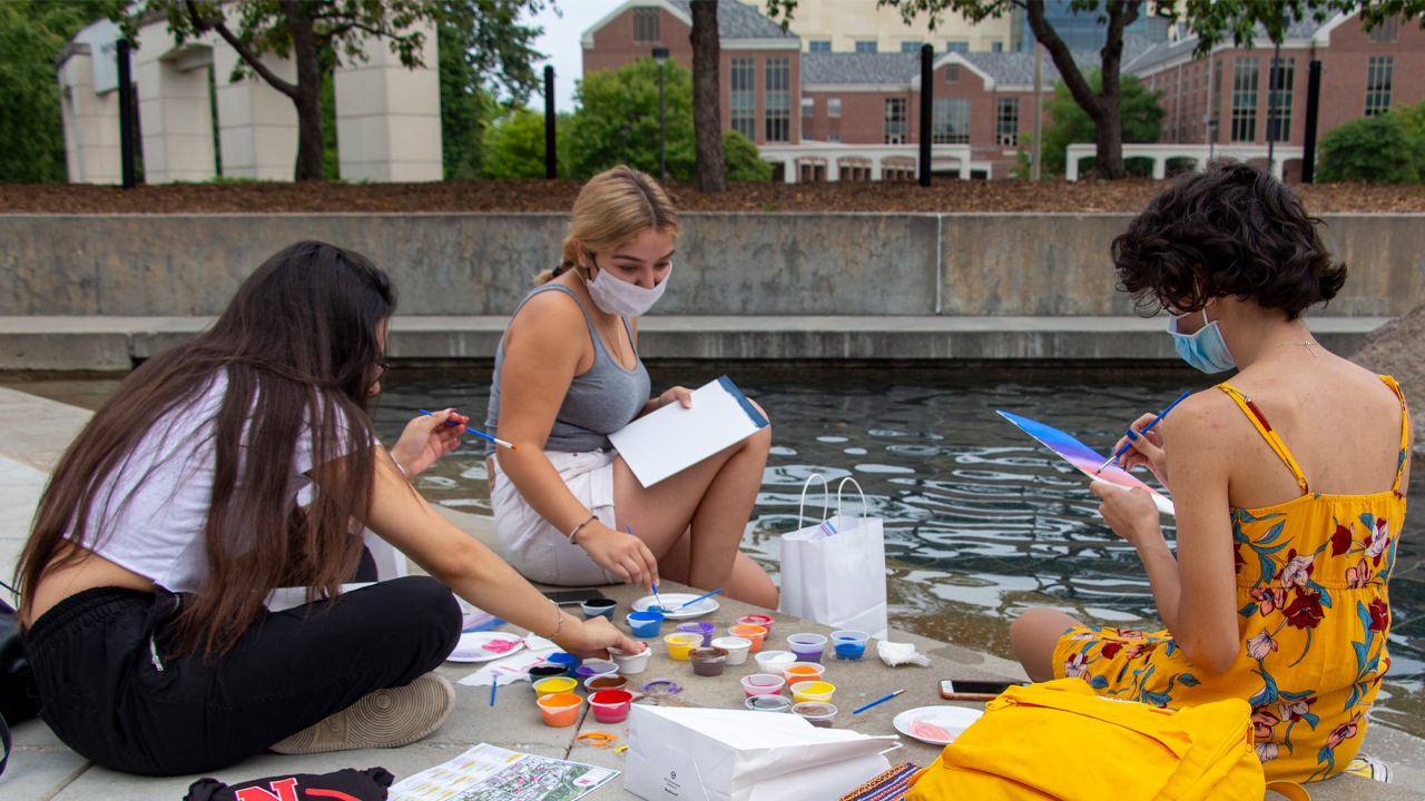 Students painting at a fountain